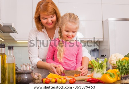 Mother and daughter cutting vegetables in kitchen