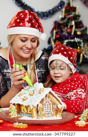 Mother and daughter decorate gingerbread house at Christmas