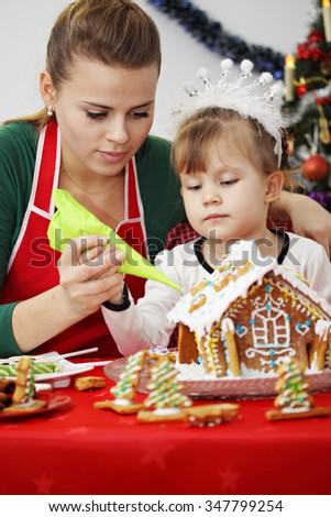 Mother and daughter decorate gingerbread house at Christmas - stock photo