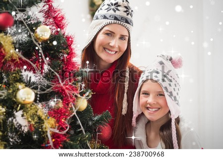 Mother and daughter decorating christmas tree against snow falling - stock photo