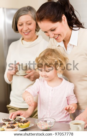 Mother And Daughter Decorating Cupcakes Sprinkles Happy Together At Home    Stock Photo