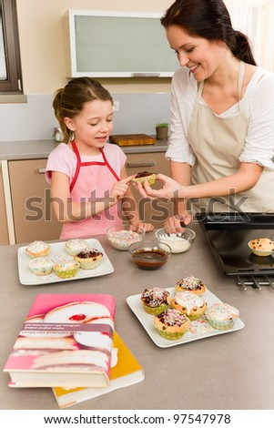 Mother and daughter decorating cupcakes sprinkles happy together at home - stock photo