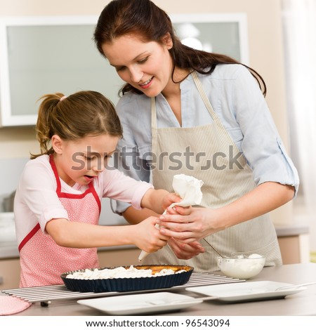 Mother and daughter decorating pie with whipped cream - stock photo