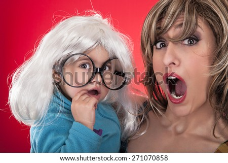 Mother and daughter disguised in a wig and glasses. with surprise. On a red background. Studio image - stock photo
