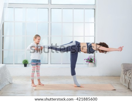 Mother and daughter do gymnastics exercises. Fitness adult woman with her child. Morning exercises, yoga - do at home all together. Grandmother and granddaughter doing yoga exercise home.