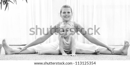 Mother and daughter doing exercise home - stock photo