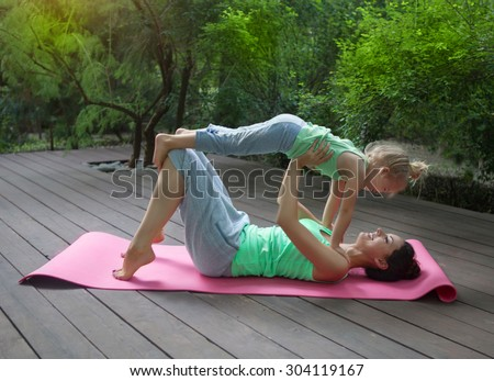 Mother and daughter doing exercise practicing yoga outdoors. Healthy lifestyle