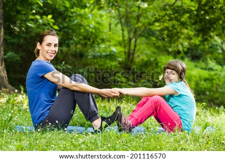 Mother and daughter doing exercises together,Mother and daughter exercising - stock photo