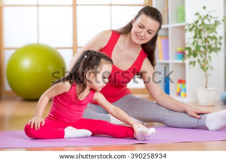 Mother and daughter doing fitness exercises on mat at home - stock photo