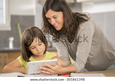 mother and daughter doing homework with a tablet