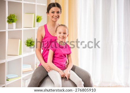 Mother and daughter doing physical exercises on fitness ball at home. - stock photo