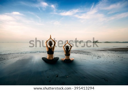 Mother and daughter doing yoga at beach - stock photo