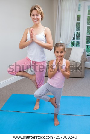 Mother and daughter doing yoga at home in the living room - stock photo