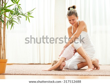 Mother and daughter doing yoga  exercise home. Mother and baby gymnastics. - stock photo
