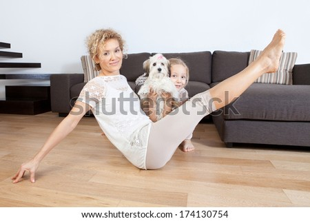 Mother and daughter doing yoga exercises with their puppy  - stock photo
