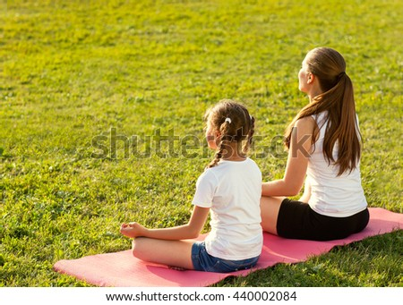 Mother and daughter doing yoga. Woman and child training in the park. outdoor sports. healthy sport lifestyle. - stock photo