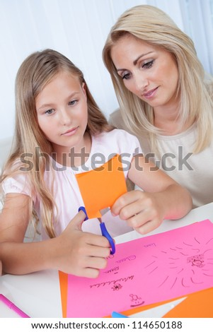Mother And Daughter Drawing Cutting Together Colorful Paper At Home - stock photo