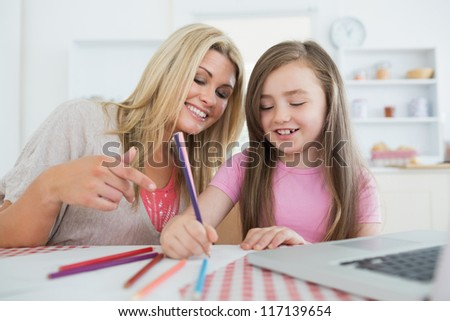 Mother and daughter drawing together at the kitchen - stock photo