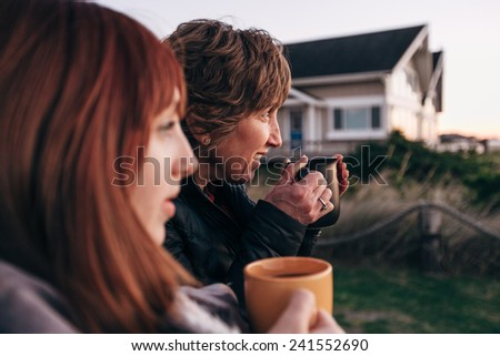 Mother and Daughter Drinking from Coffee Cups at Sunset at the Beach - stock photo