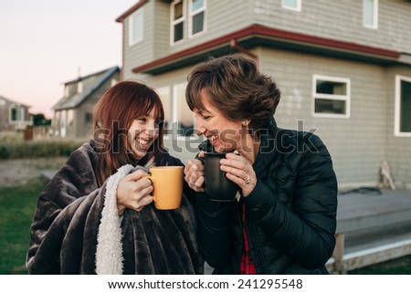 Mother and Daughter Drinking from Coffee Cups at Sunset at the Beach looking at sunset laughing and smiling with each other - stock photo
