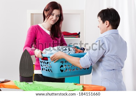 Mother and daughter during sharing house chores - stock photo