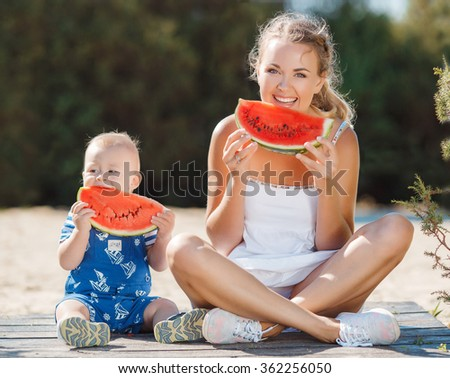 mother and daughter eat watermelon in summer park. Kid with mom at countryside eating watermelon.Happy smiling family eating watermelon in park. Happy mom and son eating watermelon  - stock photo