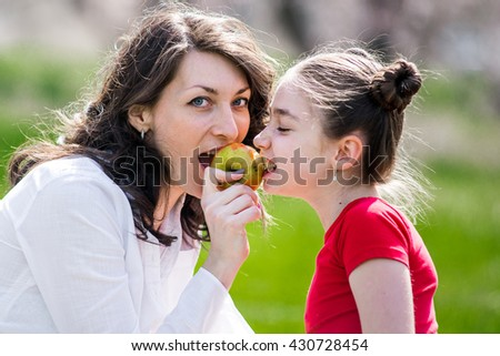 mother and daughter eating an apple in nature. Mother and her child enjoy the early spring, eating apple, happy. - stock photo