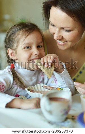 Mother and daughter eating  at  the table at home - stock photo