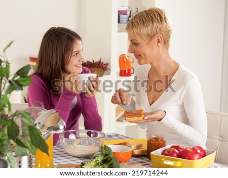 Mother and daughter eating breakfast in their home.