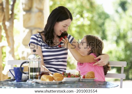 Mother and daughter eating breakfast outdoors - stock photo