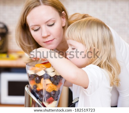 Mother and daughter eating fruits