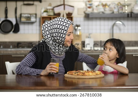 Mother and daughter eating pizza in the dining room - stock photo