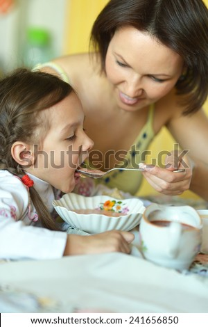 Mother and daughter eating soup at table at home
