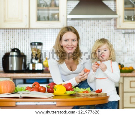 Mother and daughter eating vegetables salad in kitchen - stock photo