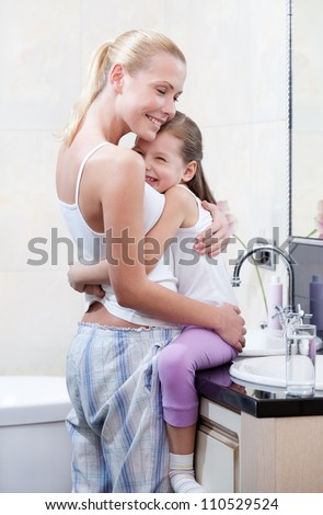 Mother and daughter embrace each other in bathroom - stock photo
