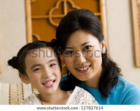 Mother and daughter embracing and smiling