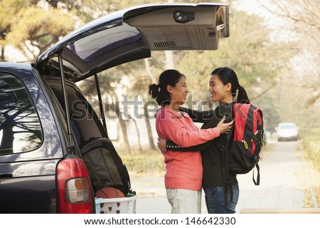Mother and daughter embracing behind car on college campus - stock photo