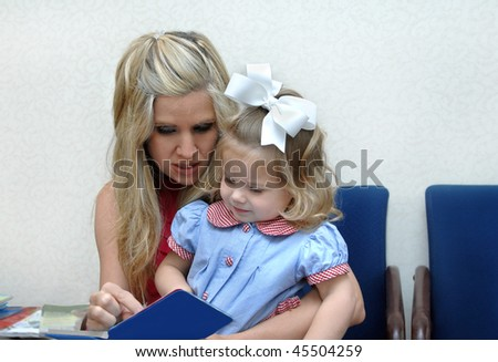Mother and daughter enjoy reading books in the waiting room at doctors office. - stock photo