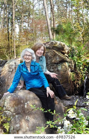 Mother and daughter enjoy springtime surrounded by foliage, trees and a trickling waterfall.  Both are smiling and sitting close together.
