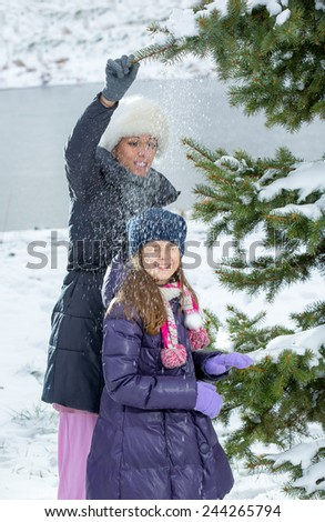 Mother and daughter enjoying beautiful winter day outdoors, selective focus - stock photo