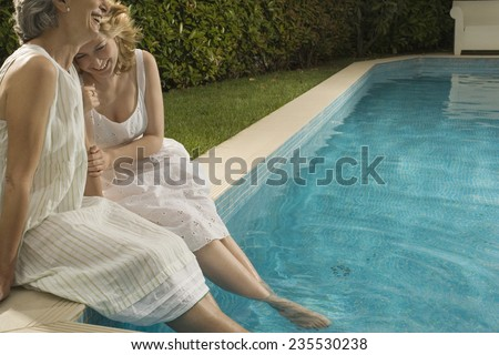 Mother and Daughter Enjoying the Afternoon with Feet in the Pool - stock photo