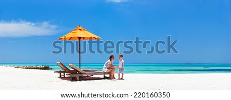 Mother and daughter enjoying time at tropical beach during luxury tropical vacation - stock photo