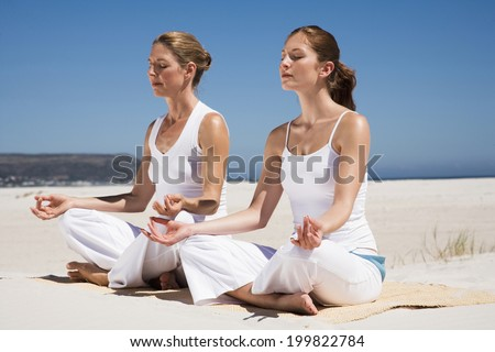 Mother and daughter exercising yoga on beach - stock photo