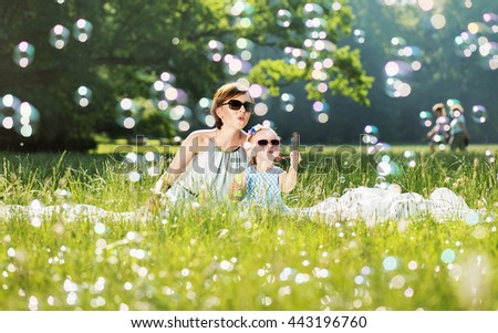 Mother and daughter family time, blowing soap-bubbles - stock photo