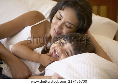 Mother and daughter giggling together - stock photo