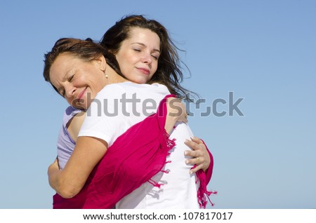 Mother and daughter giving each other a cuddle full of love and affection, with clear blue sky as background and copy space.