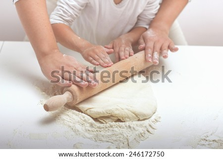Mother and Daughter Hands Kneading Dough on the table. - stock photo