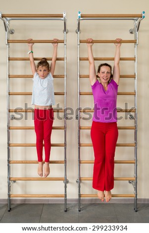 mother and daughter hanging on a horizontal bar in a gym - stock photo