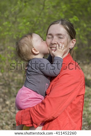 Mother and daughter. Happy young woman being kissed by a cute little girl