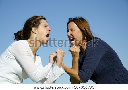 Mother and daughter having a tough argument and starting to fight. Isolated with Clear blue sky as background and copy space
